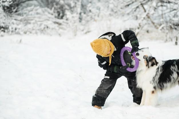 Petit garçon jouant avec un berger australien avec extracteur dans la forêt d'hiver.