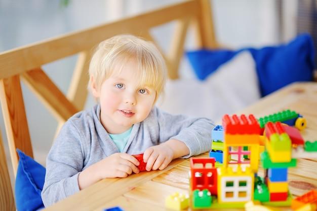 Petit garçon jouant avec des blocs en plastique colorés à la maternelle ou à la maison