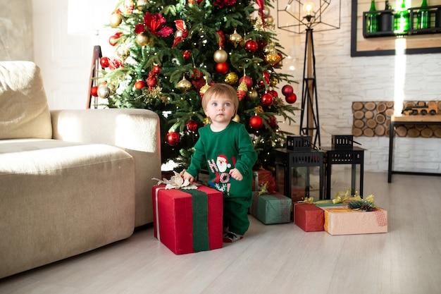Petit garçon jouant avec des coffrets cadeaux de noël