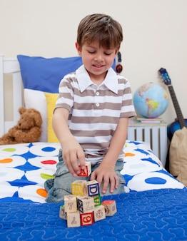 Petit garçon jouant avec des cubes alphabet dans sa chambre