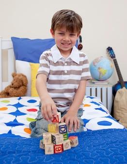 Petit garçon jouant avec des cubes alphabet
