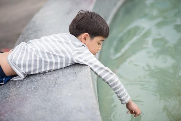 Petit Garçon Jouant Dans L'eau Photo Premium