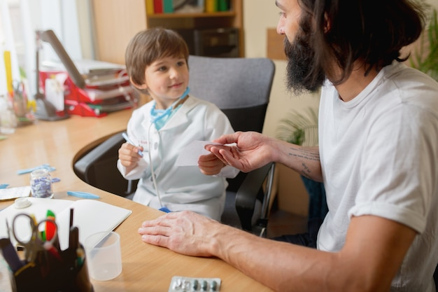 Un petit garçon jouant fait semblant d'être un médecin examinant un homme dans un cabinet médical confortable. concept de soins de santé, d'enfance, de médecine, de protection et de bonheur. s'amuser, rire tout en donnant une recette de pilules