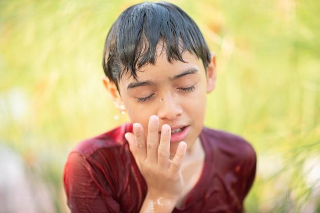 Petit garçon jouant des gouttes d'eau fontaine sous le tissu et un parapluie