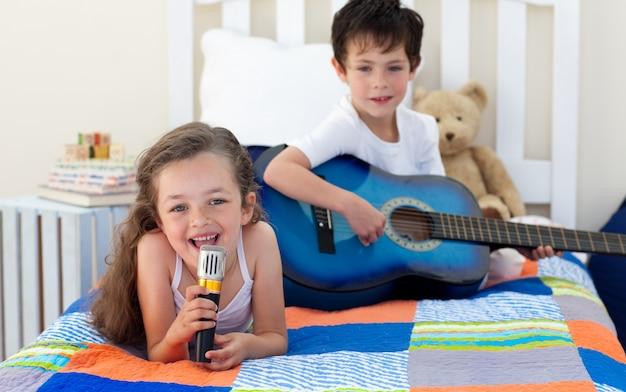 Petit garçon jouant de la guitare et sa soeur chantant