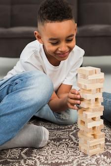 Petit garçon jouant à un jeu à l'intérieur