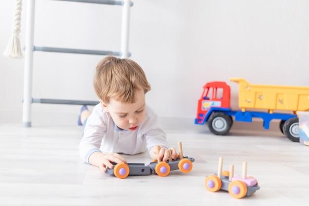 Petit garçon jouant avec des jouets en bois à la maison sur le sol