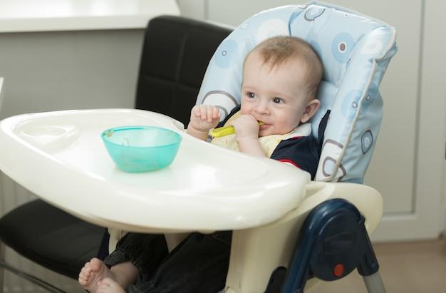 Petit garçon jouant avec de la nourriture et un plat en mangeant