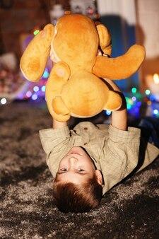 Petit garçon jouant avec un ours en peluche sur une surface de noël