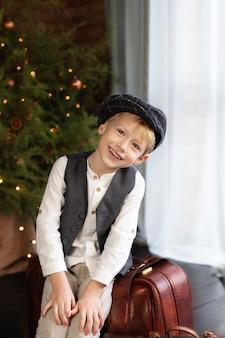 Petit garçon jouant par arbre de noël