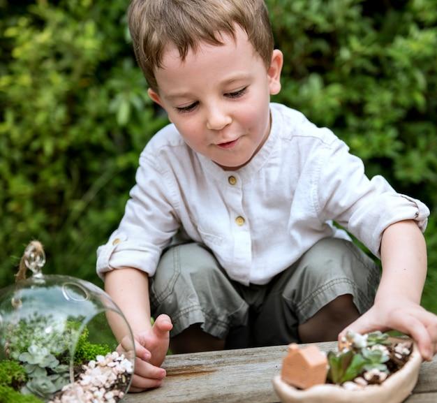 Petit garçon jouant avec des plantes