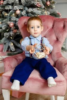 Petit garçon jouant sous le sapin de noël. enfant avec un cadeau de noël à la maison. garçon avec un cadeau de noël. enfant avec cadeau de noël. maison décorée pour les vacances d'hiver. célébration avec les enfants. les enfants jouent