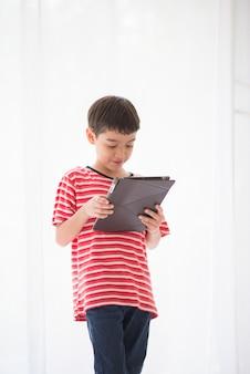 Petit garçon jouant à la tablette à la maison