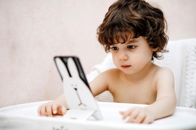 Petit garçon jouant avec un téléphone mobile. les nouvelles technologies numériques entre les mains d'un enfant. portrait de tout-petit avec smartphone