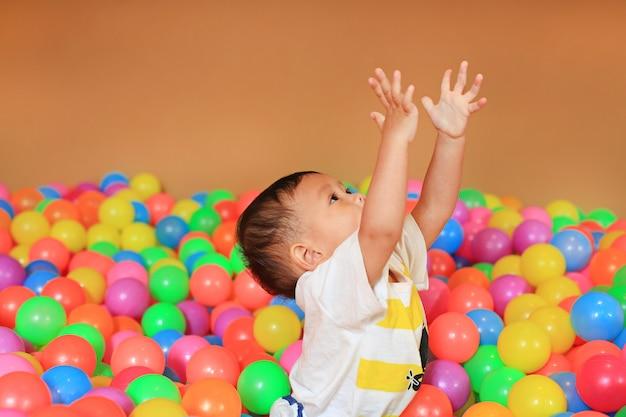 Petit garçon jouant avec terrain de jeu de boules en plastique coloré.