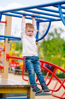 Petit garçon jouant sur le terrain de jeu.