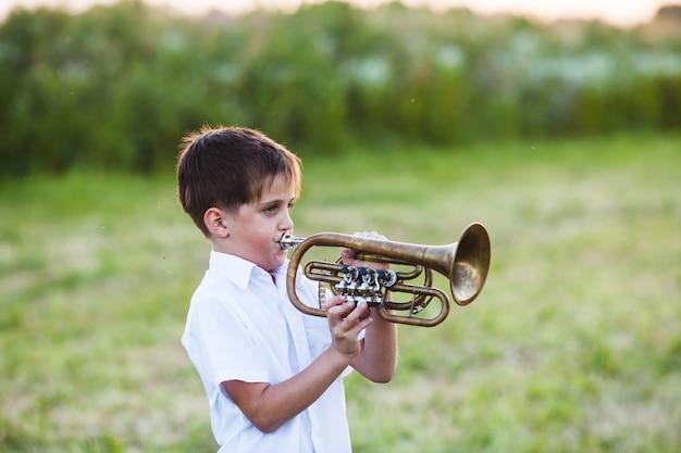 Petit garçon jouant de la trompette sur fond de nature