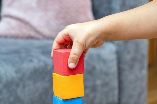 Un petit garçon joue avec des blocs de jouets éducatifs du constructeur