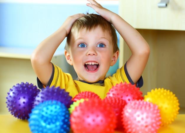 Petit garçon joue avec des boules colorées