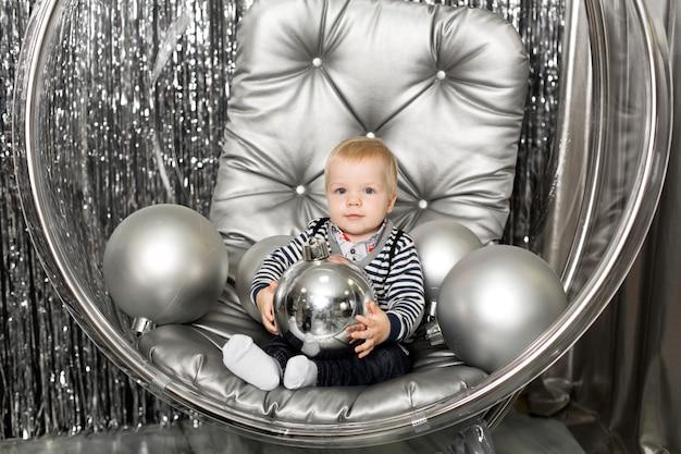 Petit garçon joue sur une chaise un bol en verre avec des boules d'argent.