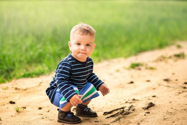 Petit garçon joue sur un chemin forestier en été