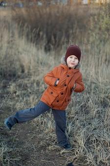 Un petit garçon joue dans un champ à l'automne dans une veste marron et un chapeau.