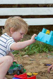 Petit garçon joue dans le sable avec des jouets en plastique. enfant jouant dans le bac à sable