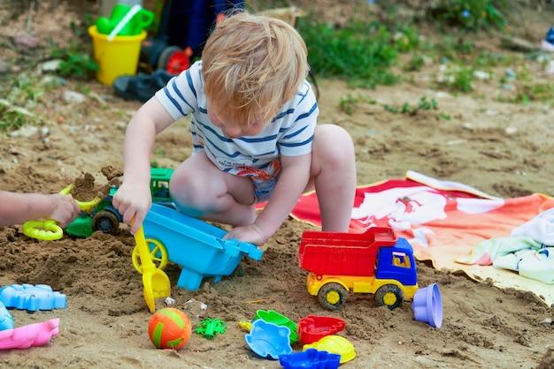 Le petit garçon joue dans le sable avec des jouets en plastique