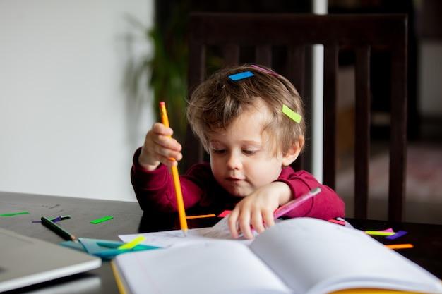Un petit garçon joue avec des documents de travail et d'autres outils pour les parents