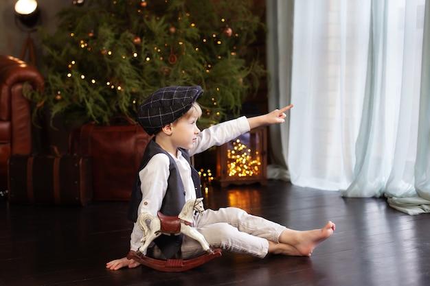 Petit garçon joue avec figurine de cheval à bascule à noël