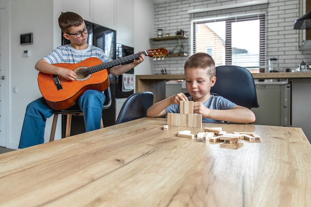 Un petit garçon joue de la guitare et son frère construit une tourelle avec des cubes en bois à la maison à la table.