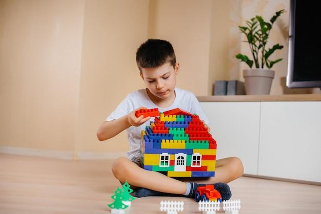 Un petit garçon joue avec un kit de construction et construit une grande maison pour toute la famille. construction d'une maison familiale.