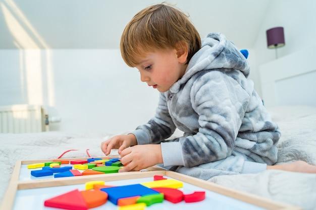 Petit garçon joue sur le lit dans un constructeur magnétique en bois