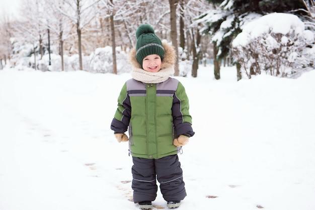 Petit garçon joue avec de la neige dans le parc