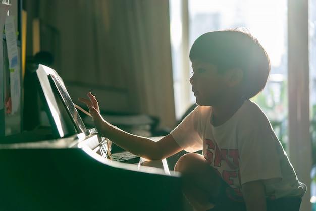 Petit garçon joue avec le piano et la tablette de musique à la maison