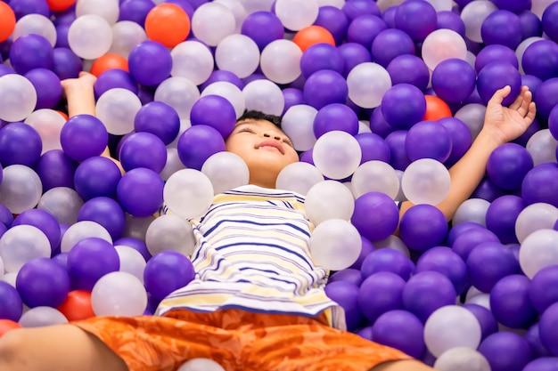 Petit garçon, jouer, dans, fosse balle, cour de récréation