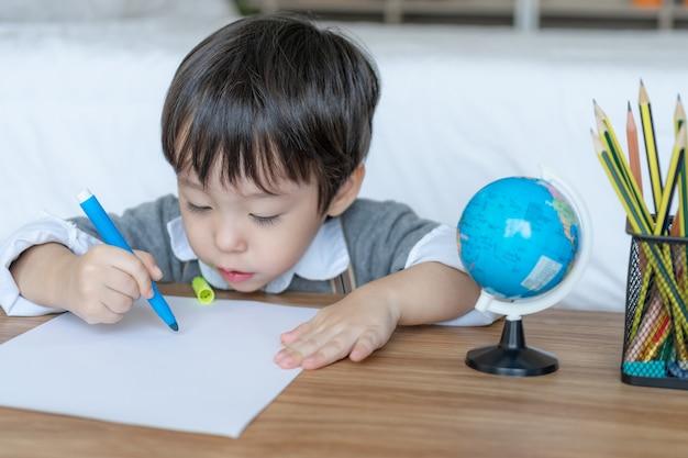Petit garçon joyeux avec crayon de couleur orange, dessin sur papier blanc
