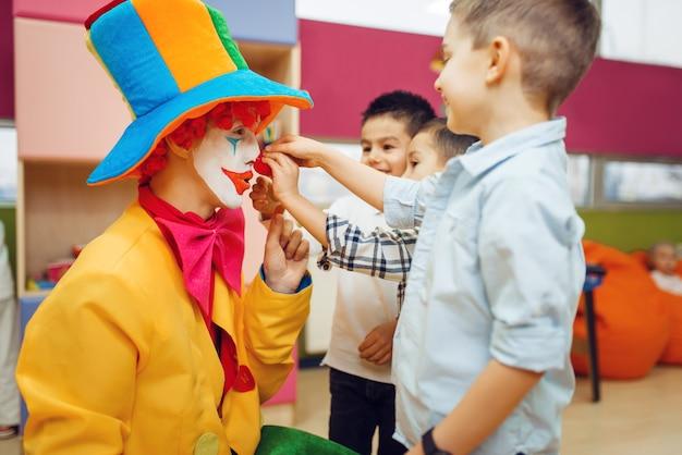 Un petit garçon joyeux touche le nez du clown rouge, des enfants jouent ensemble.