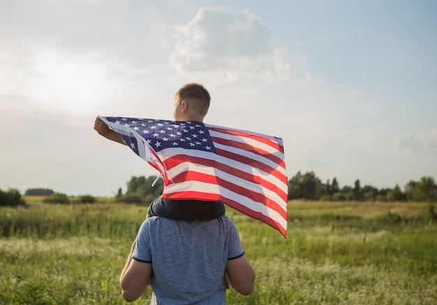 Petit garçon laisse le drapeau américain voler dans ses mains sur le vent au champ vert