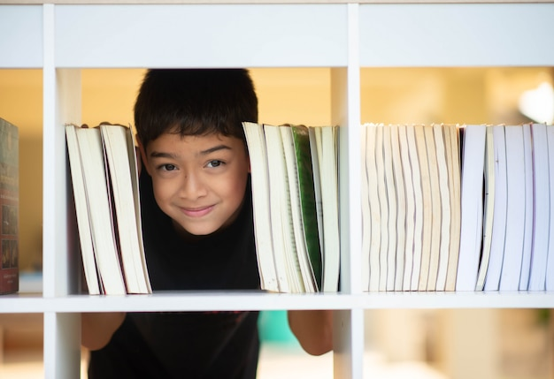 Petit garçon lisant un livre dans la bibliothèque