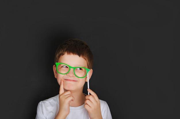Petit garçon avec des lunettes vertes près du tableau.