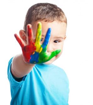 Petit garçon avec une main pleine de peinture couvrant son visage