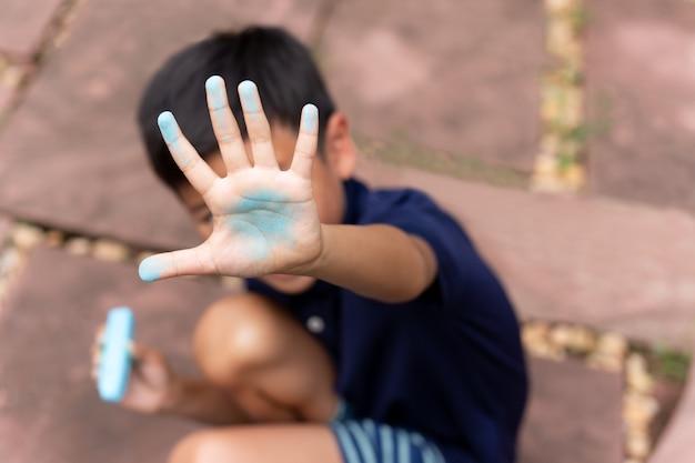 Petit garçon avec la main sale de la craie bleue