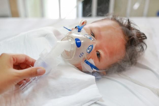 Petit garçon malade appliquant un médicament à inhaler avec un masque d'inhalation pour guérir le virus respiratoire syncytial (vrs)