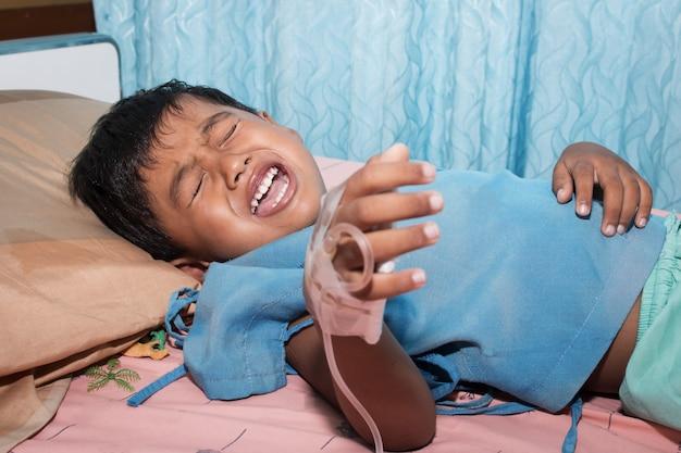 Petit garçon malade et pleurant sur le lit du patient