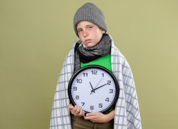 Petit garçon malade portant un t-shirt vert dans une écharpe chaude et un chapeau enveloppé dans une couverture tenant une horloge murale se sentant mal malade et malheureux debout sur un mur léger