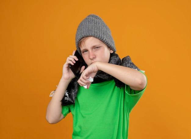 Petit garçon malade portant un t-shirt vert dans une écharpe chaude et un chapeau se sentant mal en parlant au téléphone mobile en essuyant le nez avec une serviette en papier debout sur un mur orange