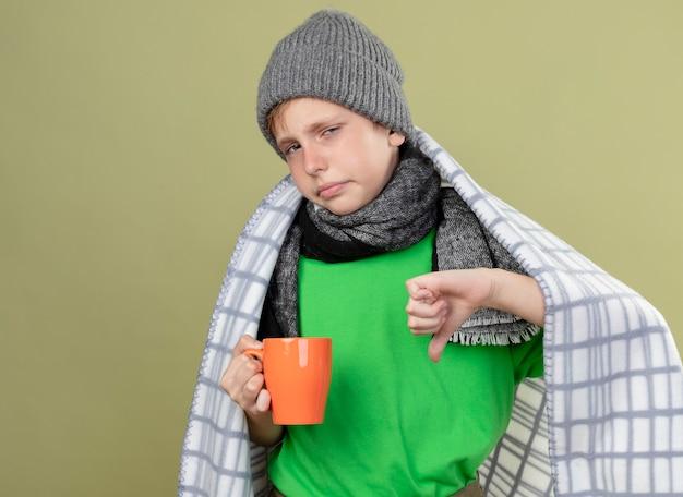 Petit garçon malade portant un t-shirt vert en écharpe chaude et un chapeau enveloppé dans une couverture tenant une tasse de thé chaud montrant les pouces vers le bas debout sur un mur léger