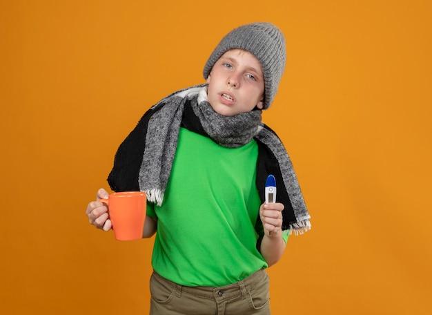 Petit garçon malade portant un t-shirt vert en écharpe chaude et un chapeau tenant une tasse de thé chaud et un thermomètre se sentant mal malade et malheureux debout sur un mur orange