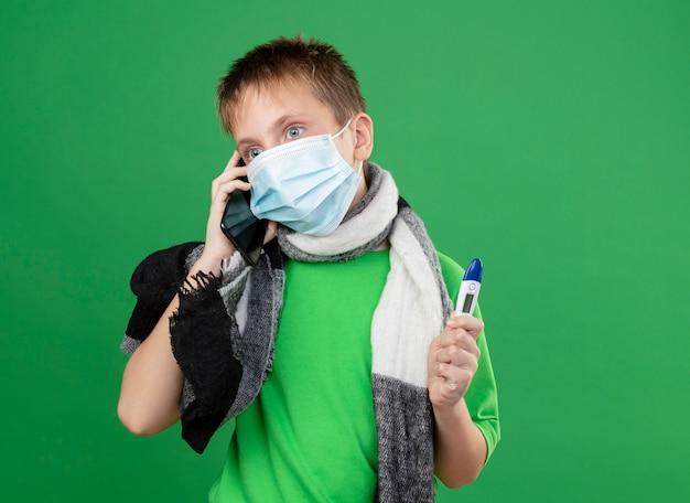Petit garçon malade en t-shirt vert et écharpe chaude autour de son cou portant un masque de protection du visage tenant un thrémomètre parlant au téléphone mobile à la peur debout sur le mur vert